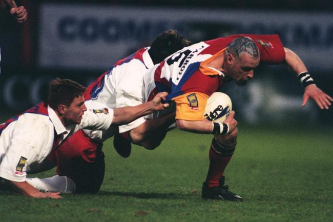 London Broncos' Bernard Carroll, right, is tackled by Paris St Germain players