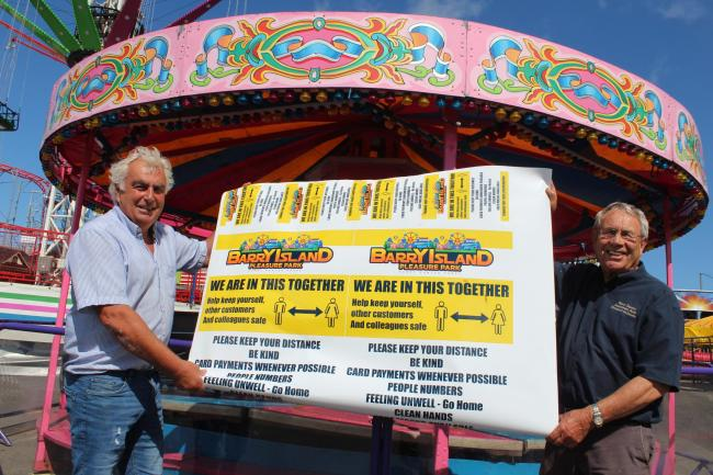 Barry Island Pleasure Park owner, Henry Danter (right) signs the covid-safe way to go
