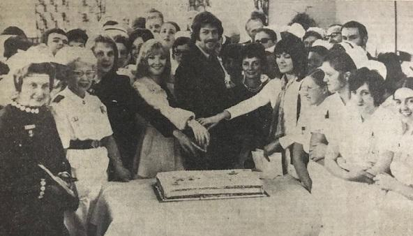 "Keith Potger, with the help of ""New Seekers"", cuts the cake especially made for the nurses' prize day at sully Hospital. On the right is Matron, Miss S. P. Turvey"
