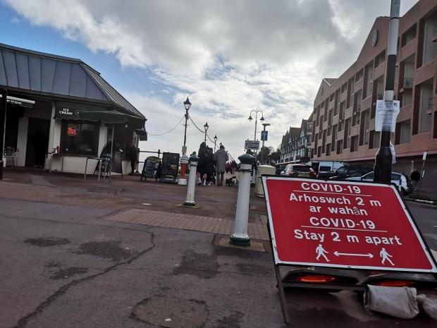 Penarth Times: Social distancing signs remain after the road had to be temporarily closed due to people packing the Esplanade over Christmas