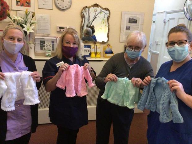 Penarth Times: Marilyn with care home staff and her wonderful creations for the newborns