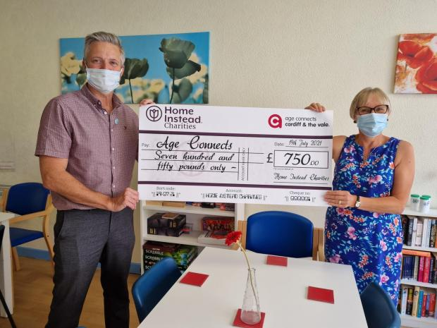 Penarth Times: Owner of Home Instead Cardiff, Phil Batchelor presenting Nona Hexter from Age Connects with a donation cheque