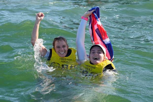 Penarth Times: Hannah Mills and Eilidh McIntyre celebrate their golds in the sea (Gregorio Borgia/AP)