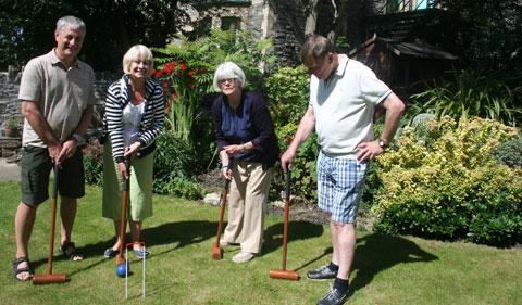 Tricia Griffiths (2nd right) in her garden at Waltham House, Bradford Place, demonstrating to visitors (l-r) Tony Martin-Jones and Lynne and Tom Lafford how to play croquet. Pictures: Glyn Paul