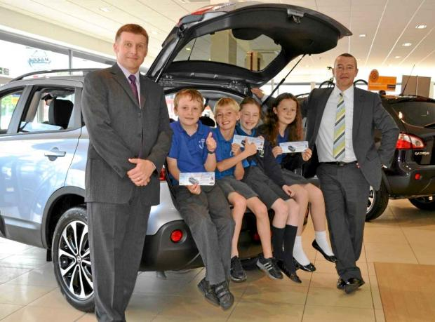 RAISING FUNDS: Mark Chapple, deputy headteacher at St Joseph's RC Primary School with pupils along with the Nissan Qashqai up for grabs in the raffle and Stephen Peach, deputy business manager at Wessex Garages.