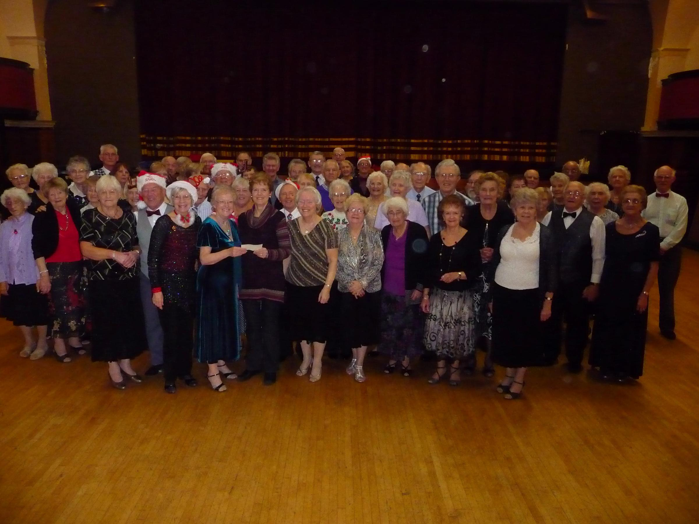 FUNDRAISERS: Members of the Paget Rooms tea dance present a cheque to a representative of the Marie Curie Hospice