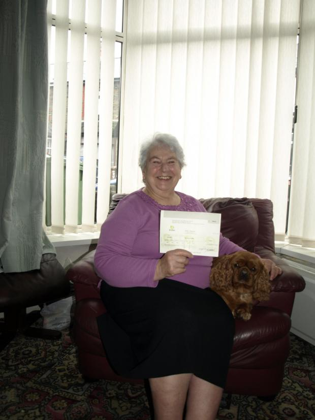 Penarth Times: LUCKY: Raffle winner Janet Griffiths, of Caerphilly, with her cheque at home