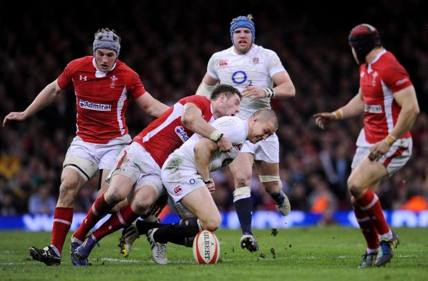 Penarth Times: England's Mike Brown (centre right) fumbles the ball as he is tackled by Wales Alex Cuthbert (centre left) during the RBS Six Nations match at the Millennium Stadium, Cardiff. PRESS ASSOCIATION Photo. Picture date: Saturday March 16, 2013. See PA stor