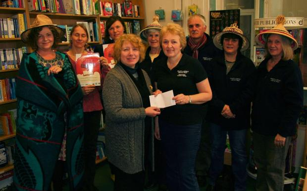 DONATION: (back row, left to right) Suki Flynn from PADLT, Mel Tuke Griffin and Fay Blakeley of the Penarth Book Festival, Rosemary Dix, Rev. Peter Cox, Tracey Graham, Mary Anne Marsden from PADLTFront: Anne Hallett from The Penarth Boo