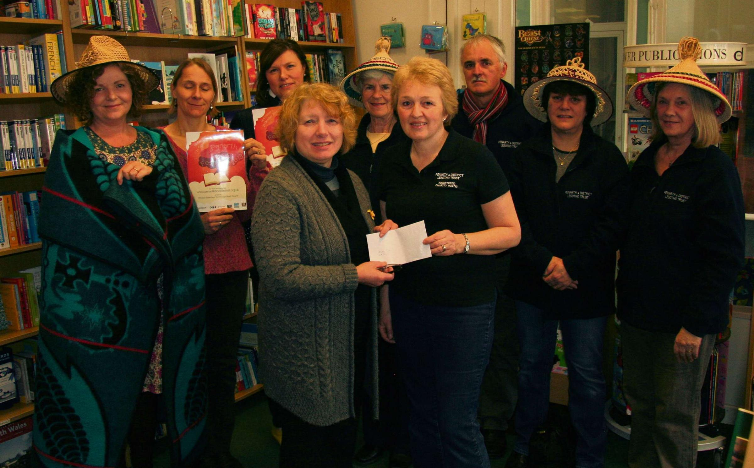 DONATION: (back row, left to right) Suki Flynn from PADLT, Mel Tuke Griffin and Fay Blakeley of the Penarth Book Festival, Rosemary Dix, Rev. Peter Cox, Tracey Graham, Mary Anne Marsden from PADLTFront: Anne Hallett from The Penarth Book Festival team pre