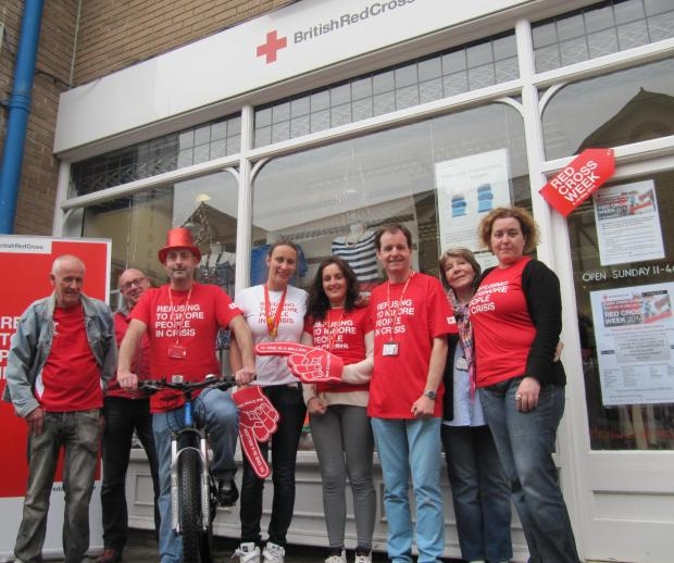 CYCLE CHALLENGE: Stuart Gillies on his bike outside Penarth's British Red Cross charity shop with employees and volunteers (5986932)