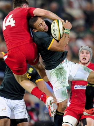 South Africa's Bryan Habana, center, takes possession of the ball from Wales' Alex Cuthbert during their rugby test match in Durban, South Africa Saturday, June 14, 2014. (AP Photo). (7157983)