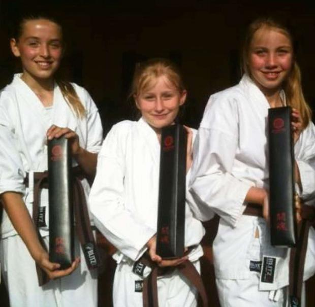 Penarth Times: PRESENTATION BOXES: Penarth Karate Club trio - from left, Jessica Jones, Lucy Roderick and Olivia de'Claire - with their Japanese silk black belts presentation boxes.