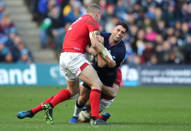 Penarth Times: BIG HIT: Hadleigh Parkes tackles Adam Hastings