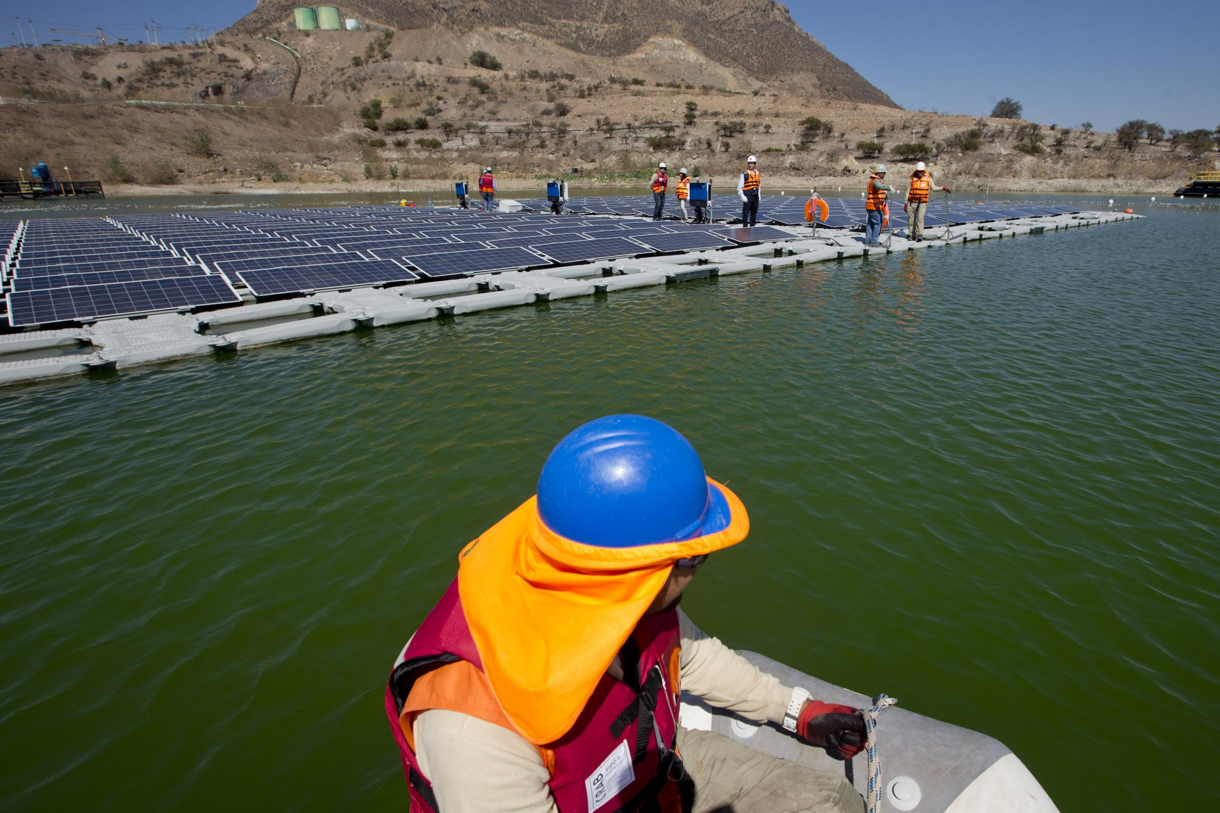 A worker on a boat approaches a floating island of solar panels