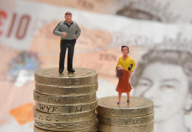 Embargoed to 0001 Saturday December 23..File photo dated 27/01/15 of plastic models of a man and woman standing on a pile of coins and bank notes. Men are significantly more likely than women to try to evade paying tax, researchers say. PRESS ASSOCIATION
